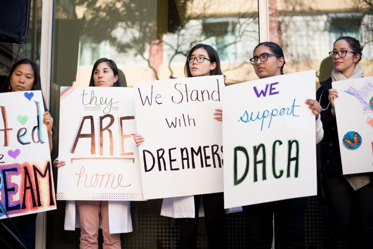 Five women of various ethnicities holding pro-Dreamer, pro-DACA protest signs.