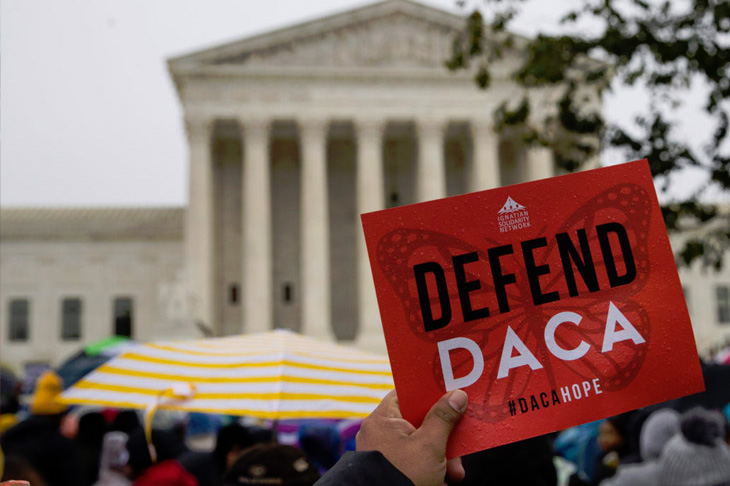"""A demonstrator holds up a """"DEFEND DACA #DACAHOPE"""" sign in front of the U.S. Supreme Court... on a rainy day."""