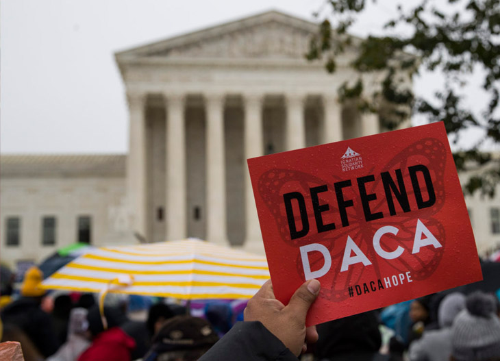 "A demonstrator holds up a ""DEFEND DACA #DACAHOPE"" sign in front of the U.S. Supreme Court... on a rainy day."